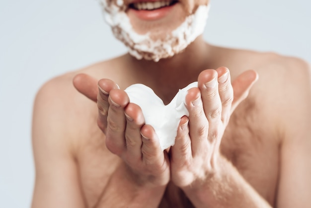 Young red haired guy smears shaving cream on stubble