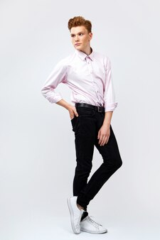 분홍색 셔츠와 바지를 입은 젊은 red-haired 남자
