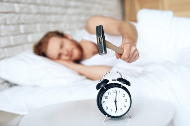 Young red haired man hammers alarm clock. lack of sleep.