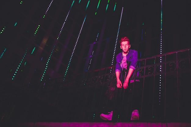 Молодой красный с волосами человек на черной предпосылке ночи. огни ночного города. на модель падает свет от наружной рекламы