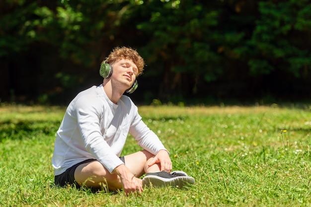 晴れた日に緑の芝生の上に座っているヘッドフォンを持つ若い赤毛の男