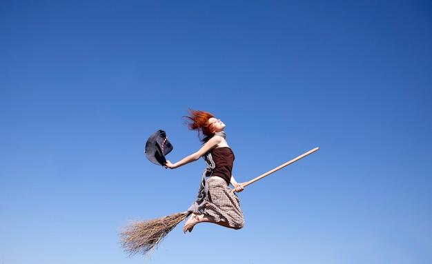 멀리 비행 빗자루에 젊은 빨간 머리 마녀