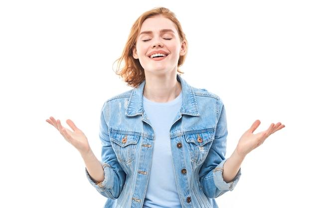 젊은 red-haired 여자는 카메라를 보고 즐긴다. 카메라를 보고 흰색 배경에 청바지에 웃는 소녀. 성공. 팔을 옆으로 벌린다