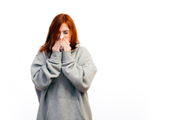 A young red-haired woman in a gray sweatshirt fell ill with a cold, closed her eyes and sneezed