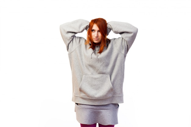 A young red-haired woman in a gray sweatshirt is holding herself with both hands behind her head