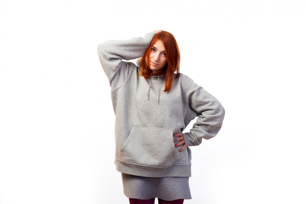 A young red-haired woman in a gray sweatshirt suffers a headache, but smiles and holds herself by the hand
