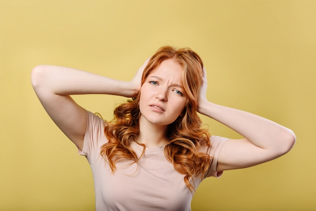 Young red-haired woman holding on to her head with two hands,