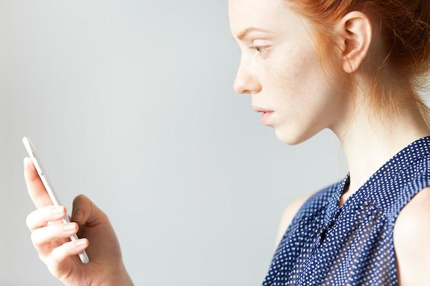 スマートフォンを保持している若い赤髪の女