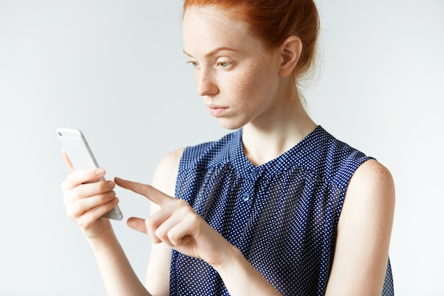 Young red-haired woman holding smartphone