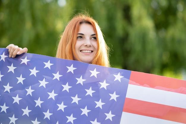 Молодая рыжеволосая женщина, держащая национальный флаг сша, стоя на открытом воздухе в летнем парке. позитивная девушка празднует день независимости соединенных штатов. международный день демократии концепции.