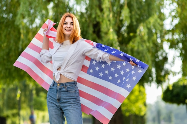 Молодая рыжеволосая женщина, держащая национальный флаг сша, стоя на открытом воздухе в летнем парке. позитивная девушка празднует день независимости соединенных штатов.