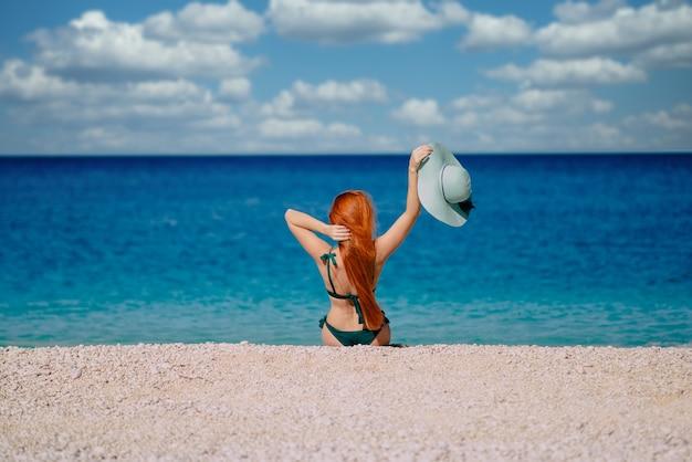 비키니 입은 젊은 나가서는 여자는 화창한 날, 후면보기에 바다로 휴가를 즐깁니다.