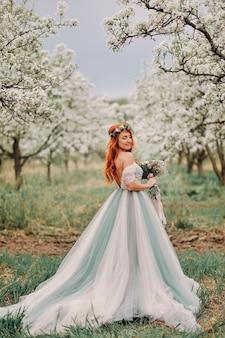 고급스러운 드레스에 젊은 red-haired 여자가 피는 정원에 서있다