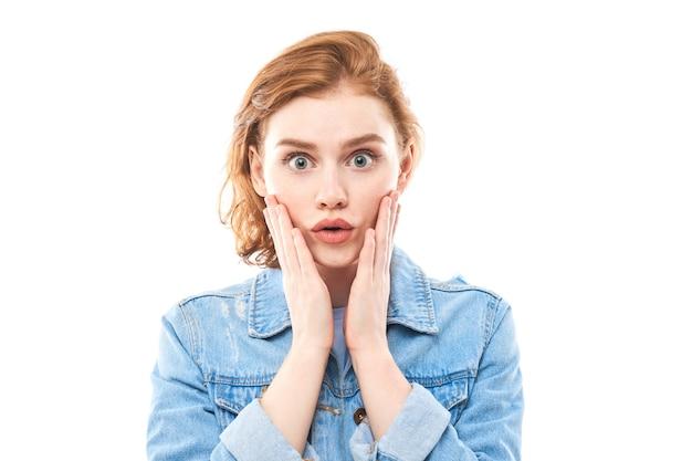 Молодая рыжеволосая женщина удивлена широко открытым ртом. шокированная девушка в джинсах на белом фоне смотрит в камеру, разводя руки в стороны