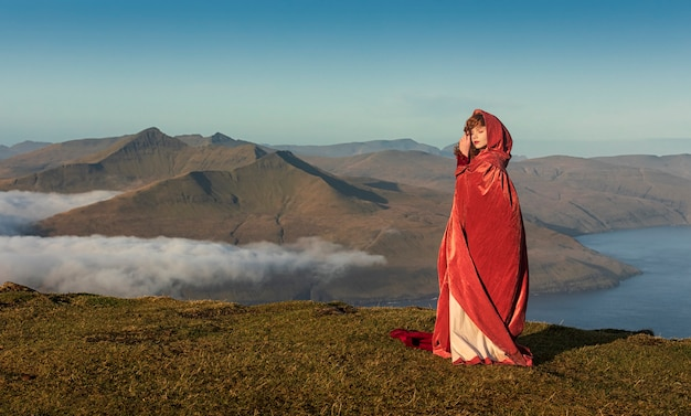 A young red-haired woman in old-fashioned clothes with a bright red cloak stays on the grass field in the highlands. faroe islands, denmark