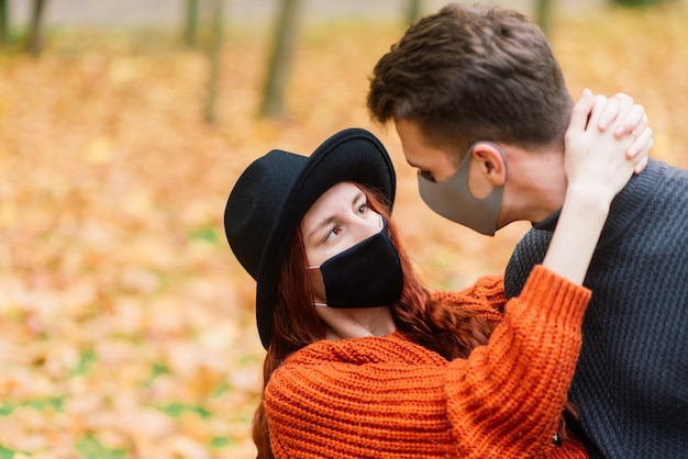 Young red haired woman puts on a face mask while walking with young man in autumn park