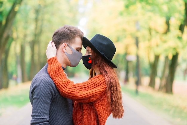 Young red haired woman puts on a face mask while walking with young man in autumn park.