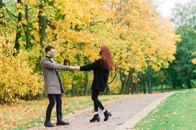 Молодая рыжеволосая женщина надевает маску во время прогулки с молодым человеком в осеннем парке