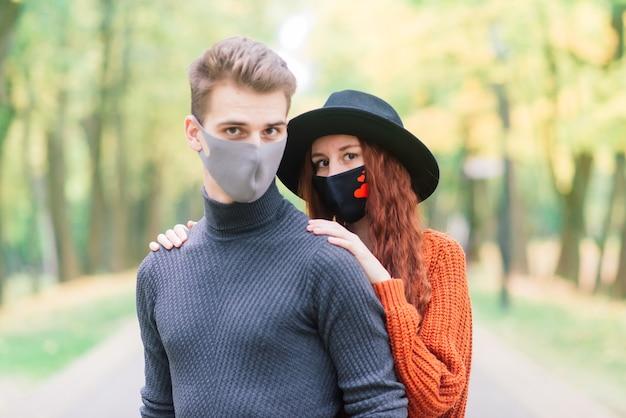 Молодая рыжеволосая женщина надевает маску во время прогулки с молодым человеком в осеннем парке.