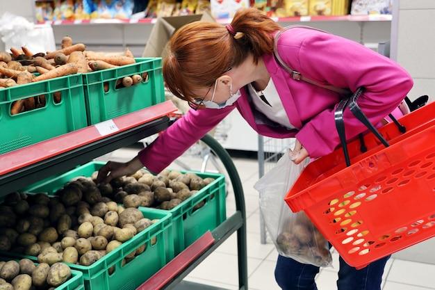 젊은 Red-haired 여자 가방에 생 감자를 넣습니다 프리미엄 사진
