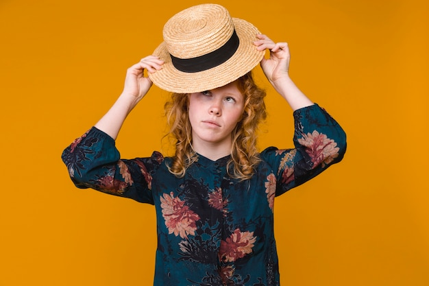 Young red haired woman putting on beige hat