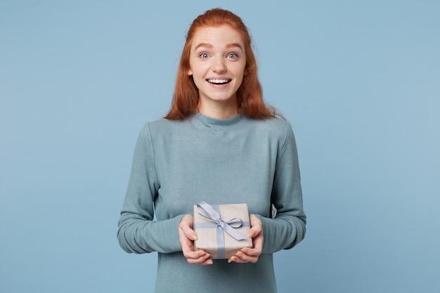 Una giovane donna dai capelli rossi ha ricevuto un regalo incartato legato con un nastro blu che lo tiene tra le mani sorridendo