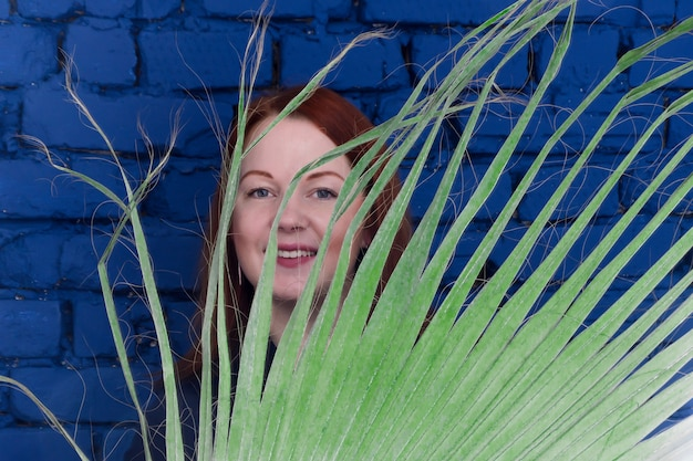Молодая рыжеволосая женщина улыбается за большой веткой пальмы на стене синего кирпича