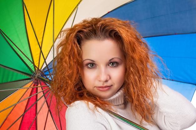 色の傘を持つ若い赤髪の女