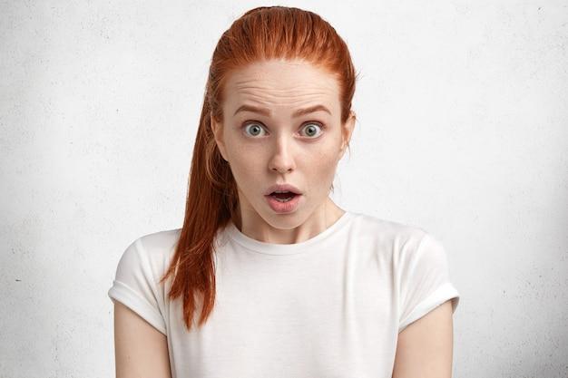 白いtシャツを持つ若い赤髪の女