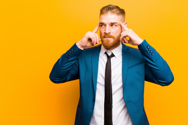 Young red head businessman feeling confused or doubting, concentrating on an idea, thinking hard, looking to copyspace on side against orange