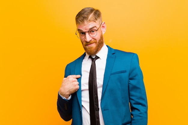 Young red head businessman feeling confused, puzzled and insecure, pointing to self wondering and asking who, me? against orange