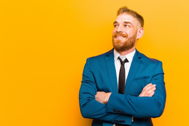Young red head businessman feeling happy, proud and hopeful, wondering or thinking, looking up to copy space with crossed arms