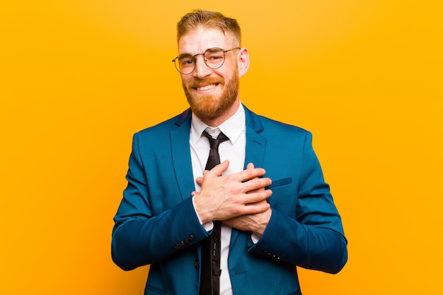 Young red head businessman feeling romantic, happy and in love, smiling cheerfully and holding hands close to heart