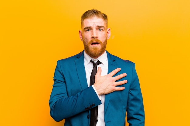Young red head businessman feeling shocked, astonished and surprised, with hand on chest and open mouth, saying who, me?  orange