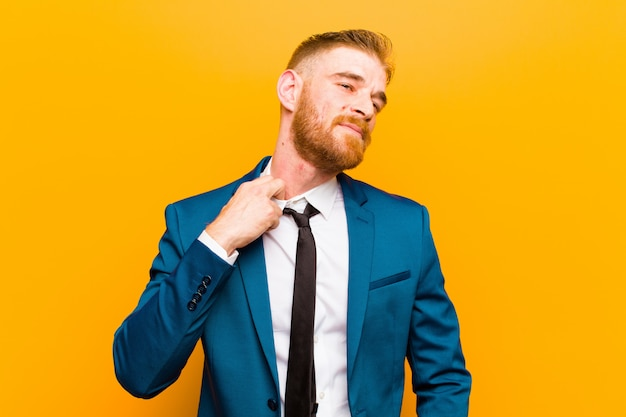 Young red head businessman feeling stressed, anxious, tired and frustrated, pulling shirt neck, looking frustrated with problem against orange background