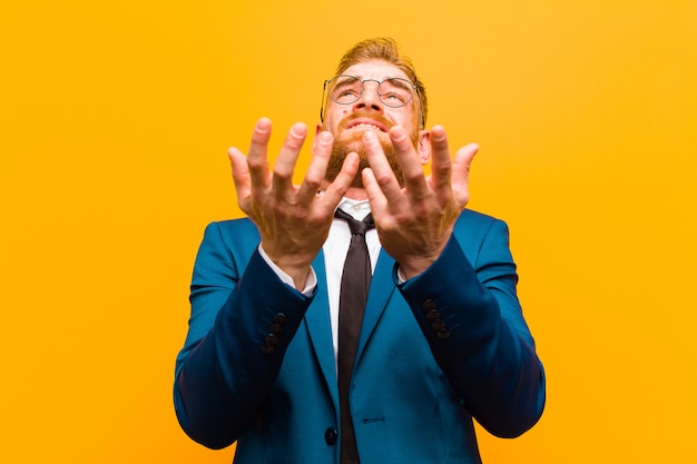 Young red head businessman looking desperate and frustrated stressed unhappy and annoyed shouting and screaming against orange background