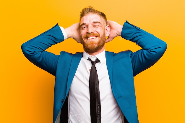 Young red head businessman looking happy, carefree, friendly and relaxed enjoying life and success, with a positive attitude on orange