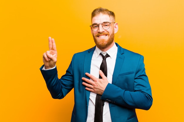 Young red head businessman looking happy, confident and trustworthy, smiling and showing victory sign, with a positive attitude