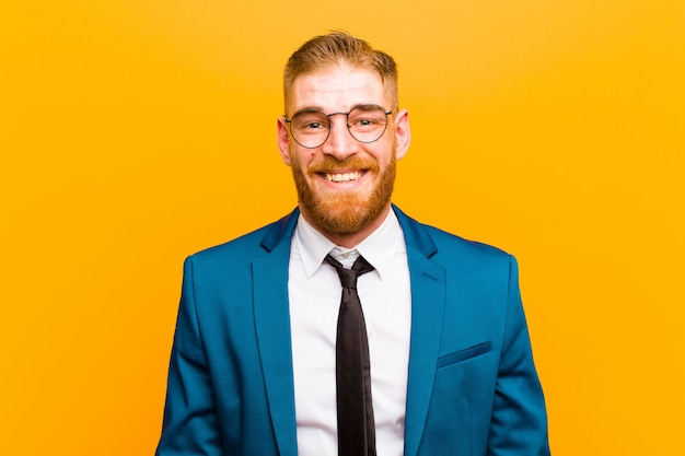 Young red head businessman looking happy and pleasantly surprised, excited with a fascinated and shocked expression on orange