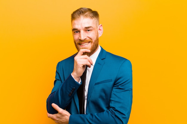 Young red head businessman looking happy and smiling with hand on chin, wondering or asking a question, comparing options