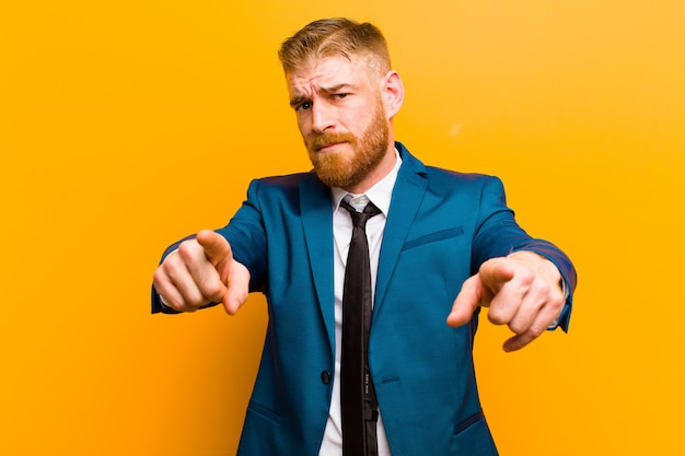 Young red head businessman pointing forward at camera with both fingers and angry expression, telling you to do your duty on orange