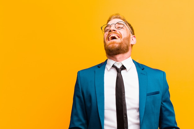 Young red head businessman screaming furiously, shouting aggressively, looking stressed and angry  orange