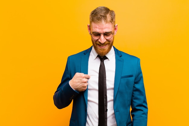 Young red head businessman smiling cheerfully and casually, looking downwards and pointing to chest