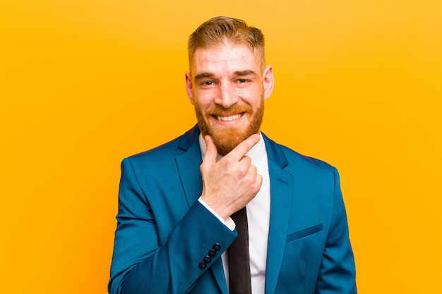 Young red head businessman smiling, enjoying life, feeling happy, friendly, satisfied and carefree with hand on chin   orange wall