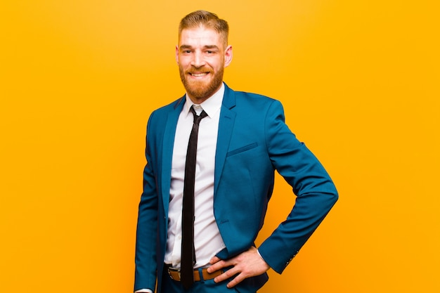 Young red head businessman smiling happily with a hand on hip and confident, positive, proud and friendly attitude