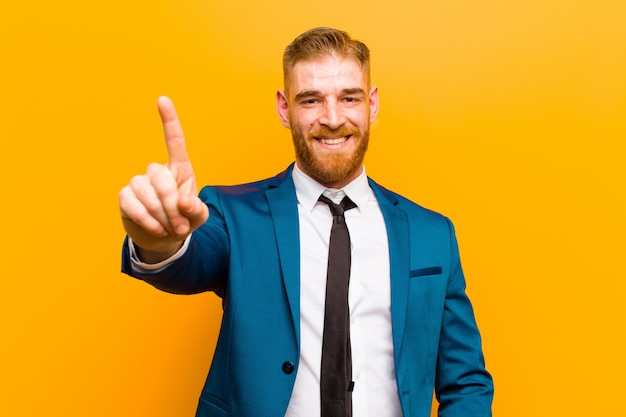 Young red head businessman smiling proudly and confidently making number one pose triumphantly, feeling like a leader against orange