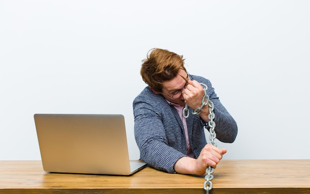 Young red head businessman working in his desk with a chain