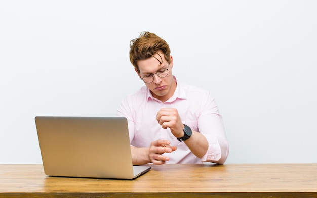 Young red head businessman working in his desk with a clock