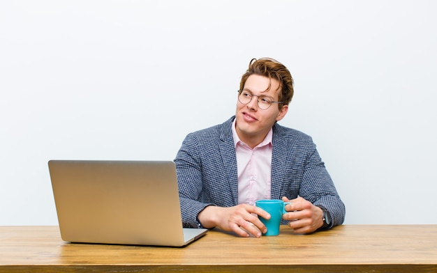 Young red head businessman working in his desk with a hot coffee cup