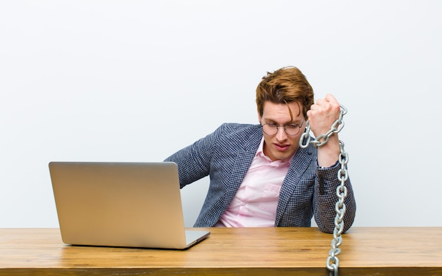 Молодой рыжий бизнесмен работает в своем столе с цепью